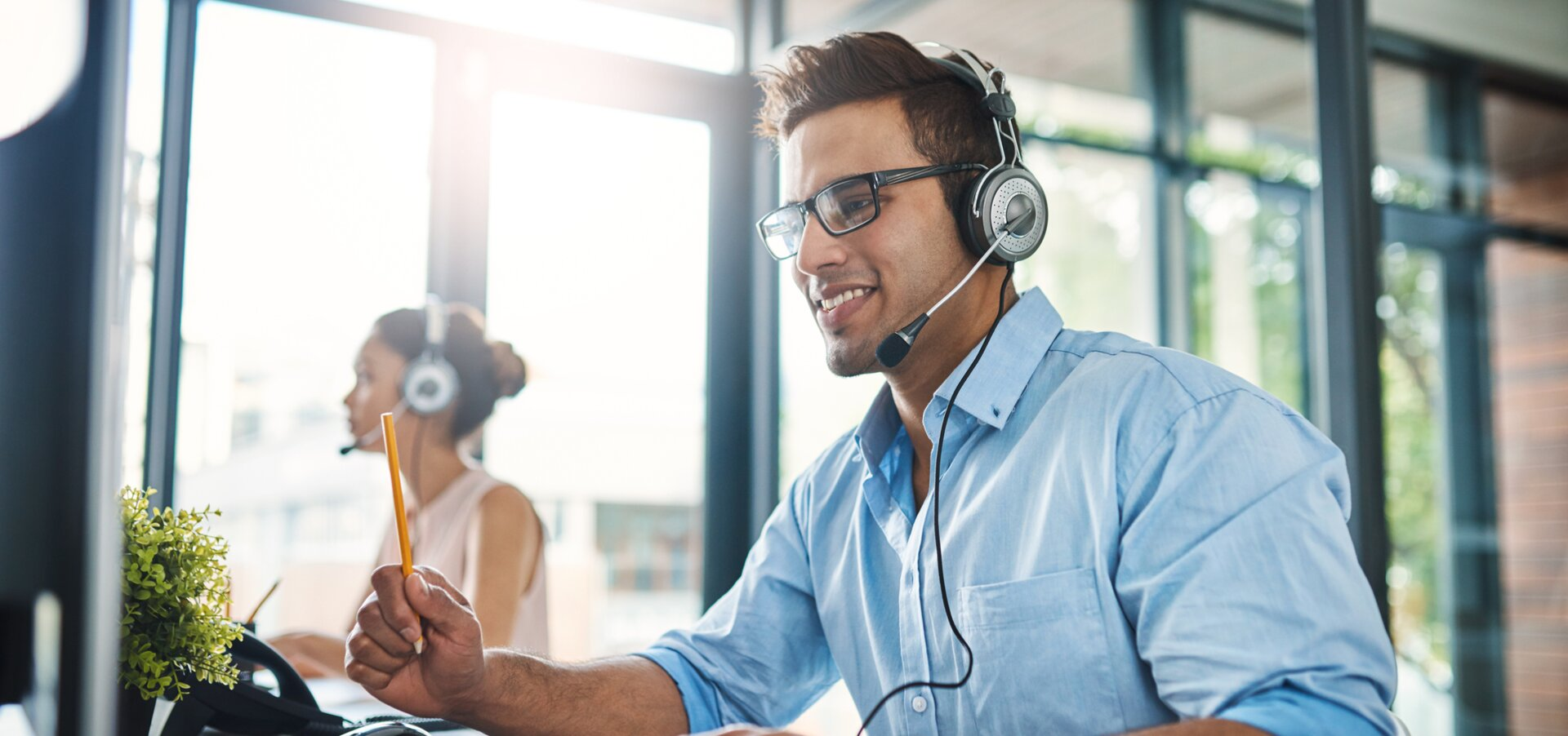 © © iStock-1132874986_PeopleImages (Cropped shot of a handsome young man working in a call center with a female colleague in the background)